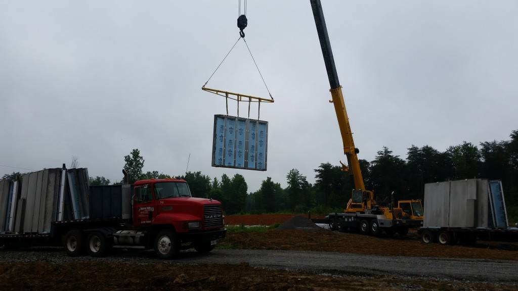 The precast Superior Walls are set in place with a crane.