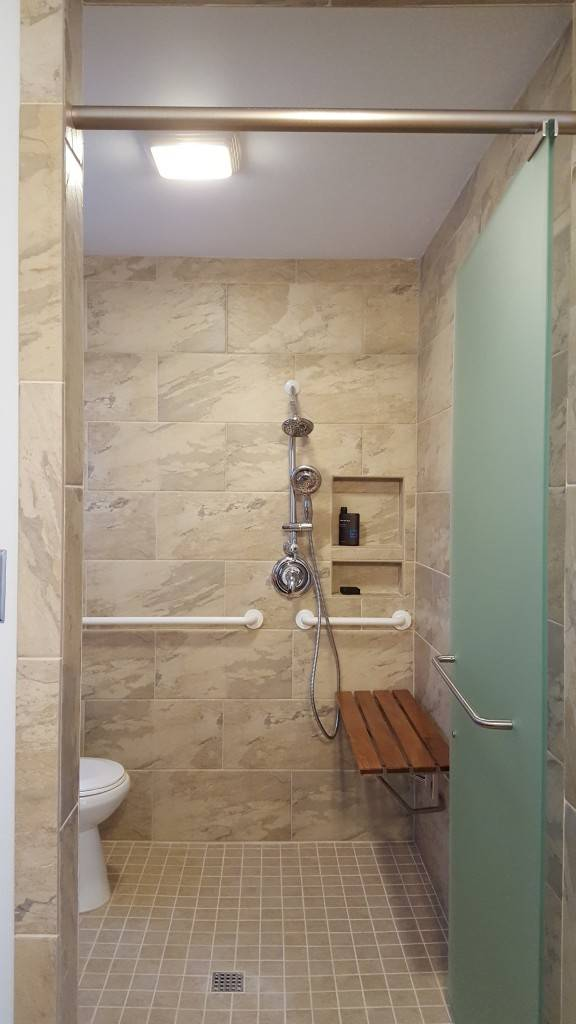 An accessible bathroom includes shower seating and grab bars
